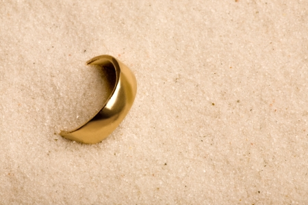 bury: A wedding ring buried in the sand - lost