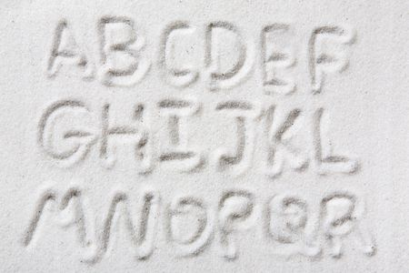 First half of an upper case alphabet written in sand - a designers tool Reklamní fotografie