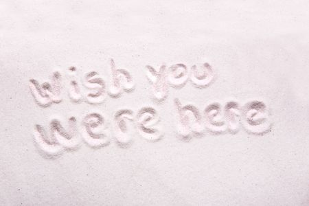 were: Wish you were here written in luxerious white sand Stock Photo