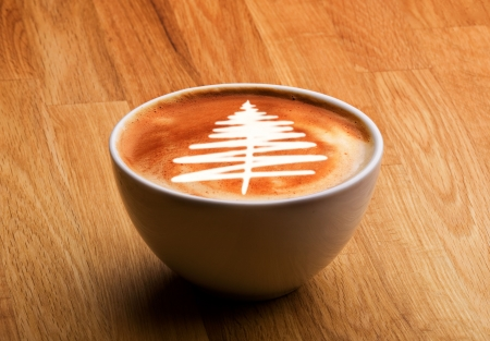 A cappuccino with a christmas tree in latte art