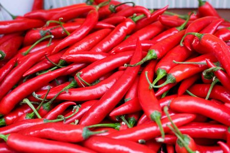 A bulk display of hot red peppers