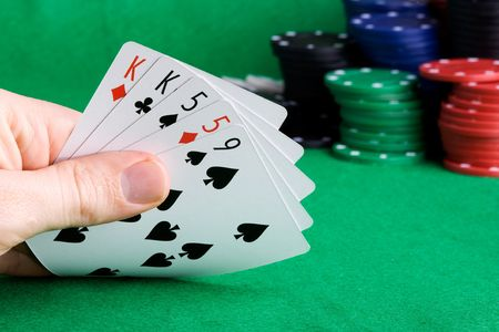 A poker hand with two pair and chips in the background photo