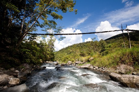 A hanging bridge over a montain stream photo
