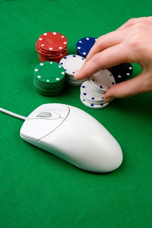 gambling parlour: An online gambling concept - computer mouse, hand and casino chips