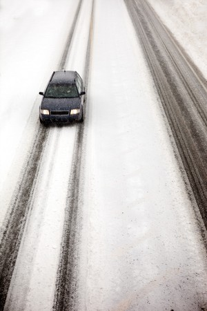 road conditions: A car travelling in a snow storm