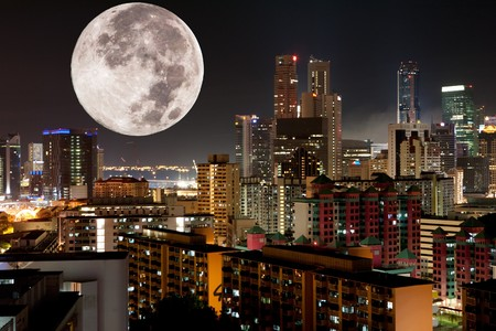 over the moon: A very large moon rising over a metropolis