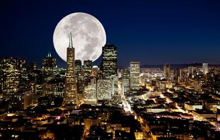 A full moon over a urban metropolis Stock Photo