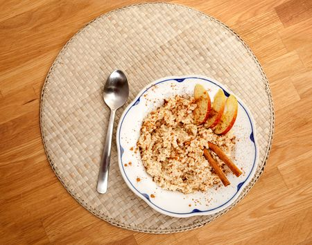 A bowl of porridge with apple and cinnamon spices viewed from above photo