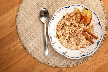 A bowl of porridge with apple and cinnamon spices photo