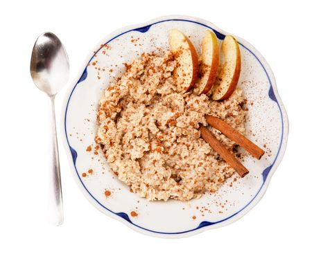 A bowl of porridge with apple and cinnamon spices isolated on white photo