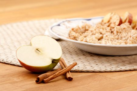 Apple Cinnamon Porridge - shallow depth of field with focus on the apple and cinnamon stick photo