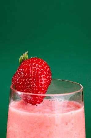 A fresh summer strawberry drink isolated on green photo