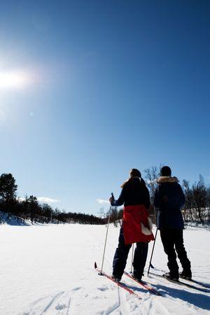 snow break: Two women in a winter landscape cross country skiing