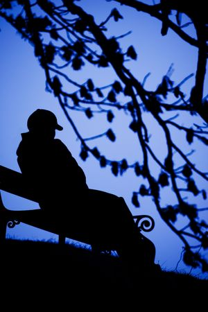 A person sitting alone on a bench Stock Photo