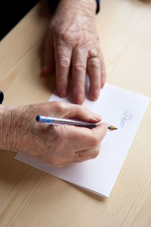 An old pair of hands writing a letter