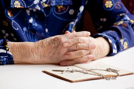 folded hands: Old folded hands in front of a book and cross.  Focus on the hands. Stock Photo