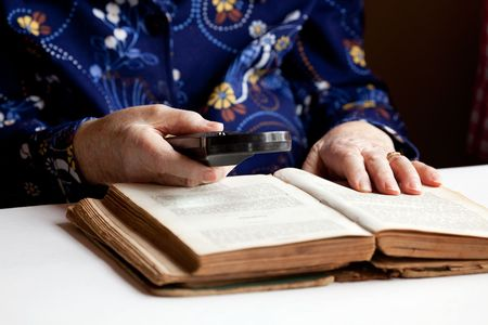 reading glass: An elderly woman reading a very old book