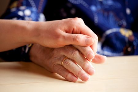 A young hand comforts and elderly hand Stock Photo