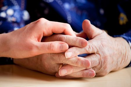 A young hand holding an elderly pair of hands Stock Photo