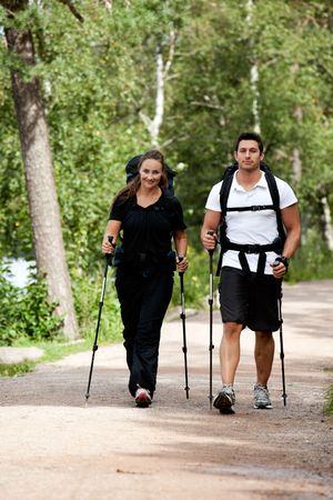 walking pole: A male and female camping in the woods walking on a path