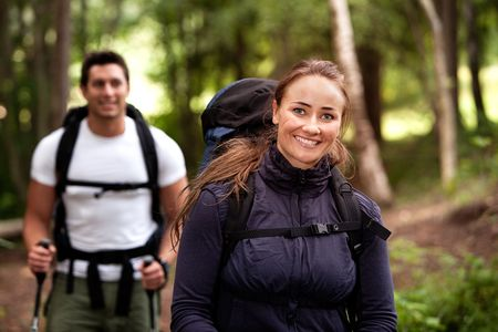 trekking pole: A pretty female on a camping trip with a male in the background