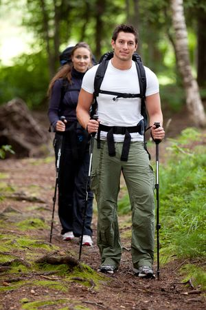 trekking pole: A man and woman on a camping trip in the forest.