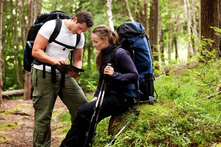 orienteering: A couple of backpackers looking at a map in the forest