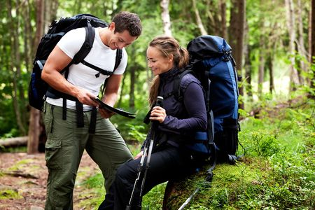 trek: A couple with smiles looking at a map in the forest