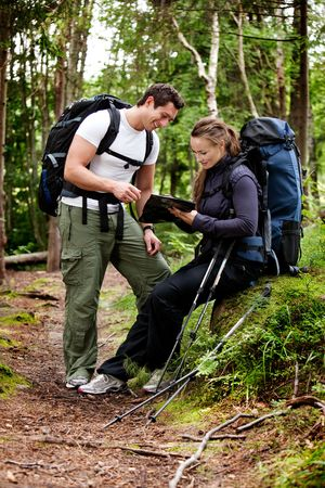 trekking pole: A couple on a backpacking camping trip looking at a map Stock Photo
