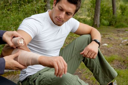 first help: A woman applying an arm bandage on a male camper - focus on male face Stock Photo