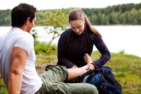 Une femme appliquant un bandage à la cheville sur un campeur mâle