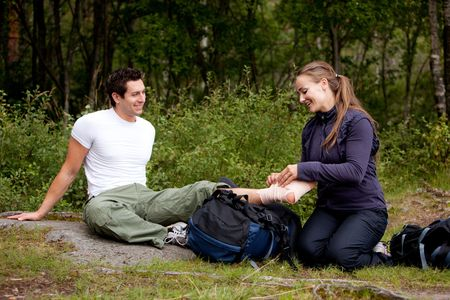 A couple camping and putting on a leg bandage photo