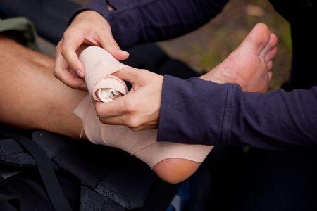 primeros auxilios: Un vendaje de tensor de pierna que se aplica al aire libre Foto de archivo