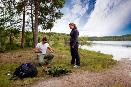 Camping lifestyle - a man and woman setting up a tent by a lake photo