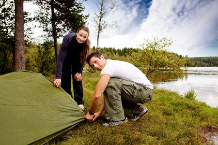 A man and woman camping - setting up a tent photo
