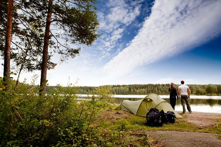 back packs: A couple camping on a lake landscape