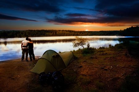 sunset lake: A pair of campers with a tent set against a beautiful sunset lake landscape