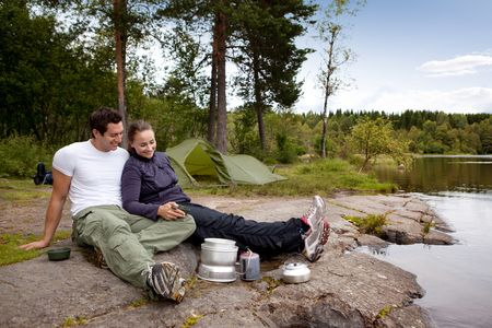 trekking: A couple camping and eating outdoors