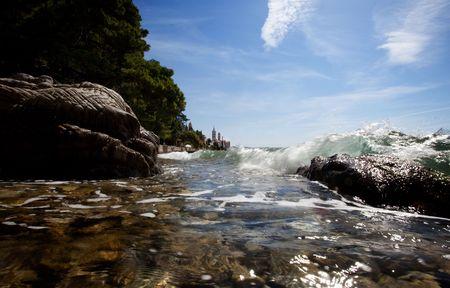 A wave splashes against rocks on the croatian coast photo