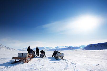 A group on a winter snowmobile adventure over a barren winter landscape photo