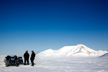 Two men on a snowmobile trip on Svalbard, Norway photo