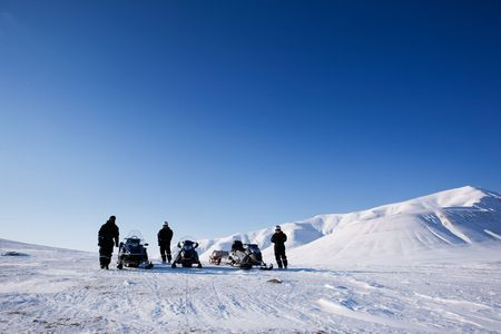 Three people with snowmobiles in an arctic landscape photo