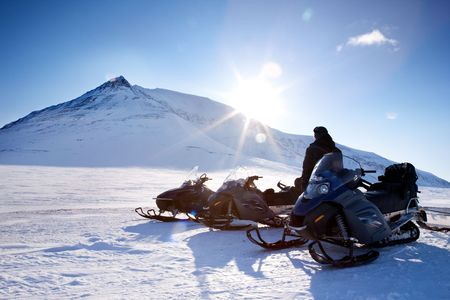 Three snowmobiles and a winter landscape with mountain photo
