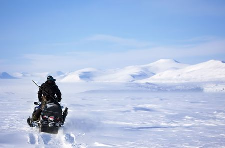 A winter landscape with a snowmobile travelling across frozen ice photo