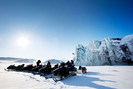 svalbard: A number of snowmobiles near a glacier in Svalbard, Norway Stock Photo