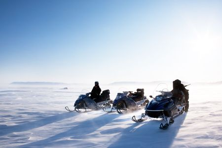 A winter landscape with blowing snow and three snowmobiles. photo