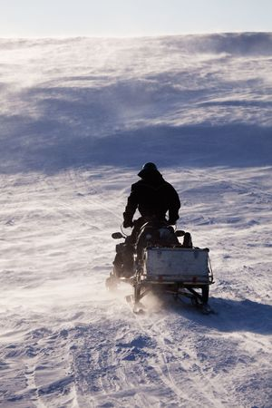 A man sitting on a snowmobile on a barren snow landscape photo