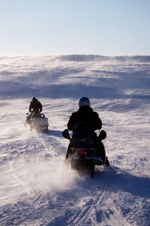 Two people riding up a hill on snowmobiles photo