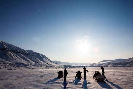 Three people on a winter snowmobile adventure in Svalbard, Norway photo