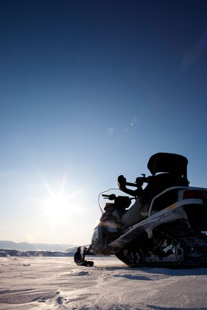 A snowmobile detail on a barren winter landscape photo